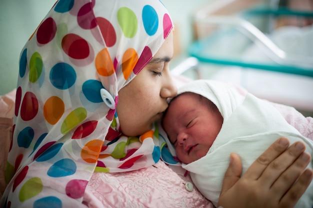 Árabe mãe muçulmana carregando seu filho na cama do hospital imediatamente após o parto