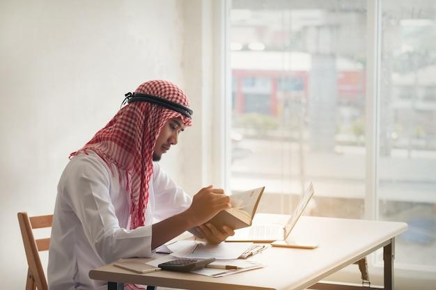 Árabe saudita homem trabalhando on-line com um laptop e lendo o livro em um escritório