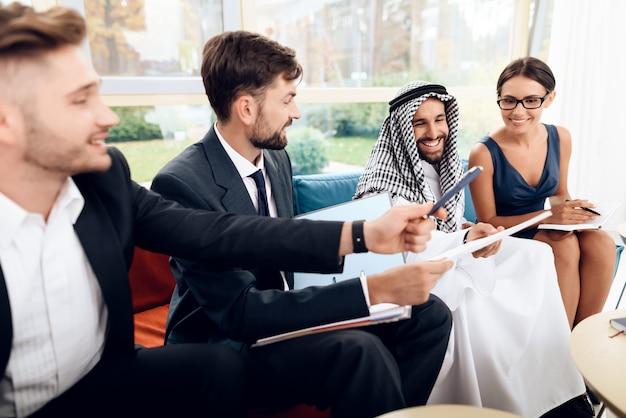 Árabes e uma mulher estão trabalhando em um escritório brilhante.