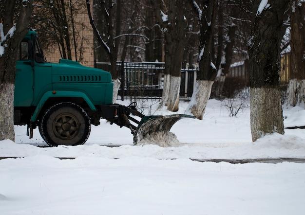 Arado de neve que remove a neve da estrada da cidade