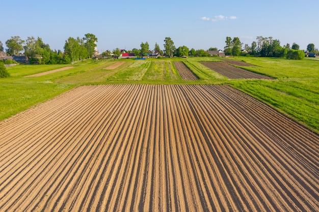 Arados sulcos para o plantio de plantas agronômicas entre o campo de grama e prados, vista aérea de cima.