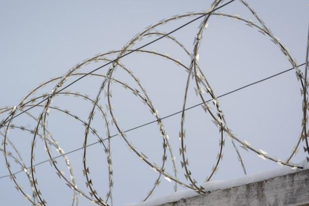 Arame farpado com tensão elétrica no topo da cerca defensiva na prisão