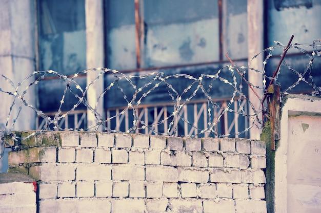 Arame farpado em uma parede de tijolos em ruínas
