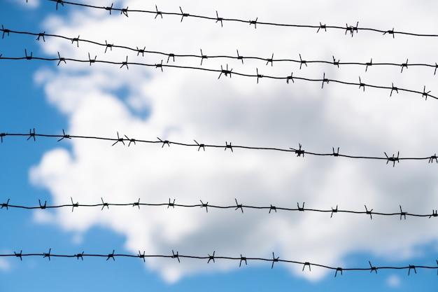 Arame farpado na fronteira do país. barbwire na cerca para proibir a passagem ilegal de estrangeiros.