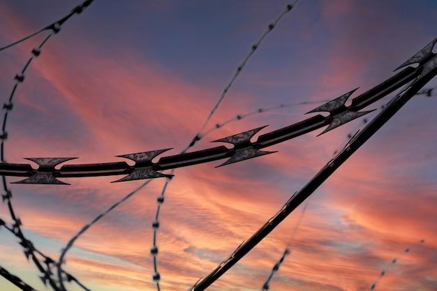 Arame farpado no fundo do céu dramático ao pôr do sol, foco seletivo