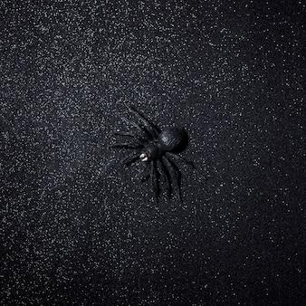 Aranha preta grande do dia das bruxas sobre o fundo escuro do brilho