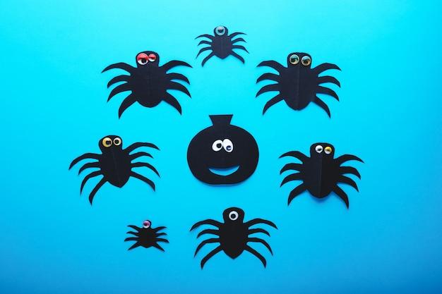 Aranhas de papel engraçadas e abóbora com olhos sobre um fundo azul. conceito de decorações de halloween. feliz dia de halloween. camada plana, vista superior. convite para festa, celebração.