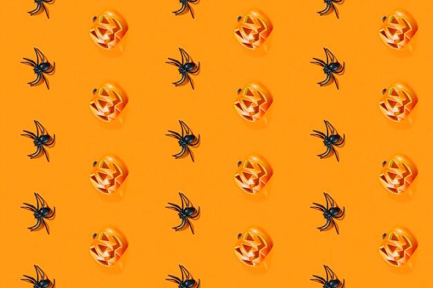Aranhas negras e abóboras de halloween colocadas em linhas