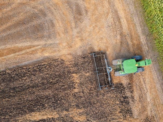Arar a terra após a colheita no campo no outono. vista aérea do drone do campo após a colheita