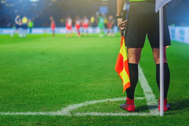 Árbitro assistente de atacante na esquina de um campo de futebol