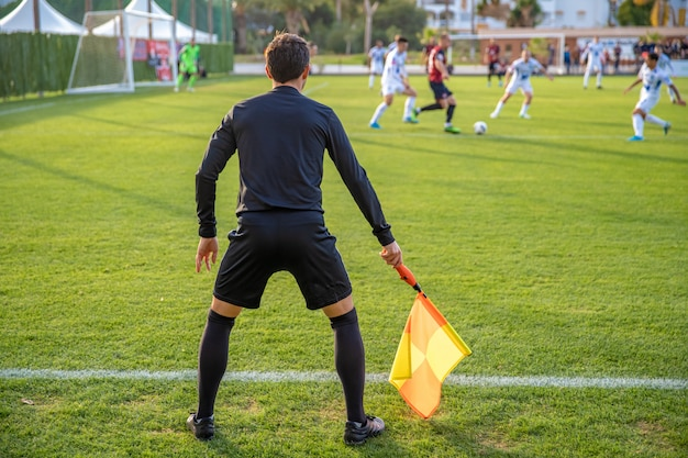 Árbitro assistente em uma partida de futebol assistindo o jogo