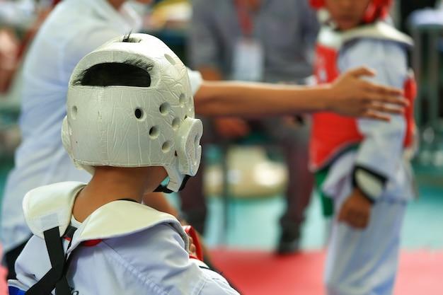 Árbitro dá sinal para jovens atletas de taekwondo