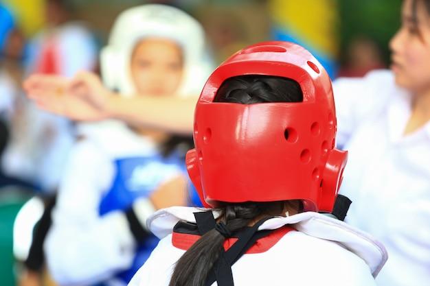 Árbitro dá sinal para meninas durante competição de luta de taekwondo