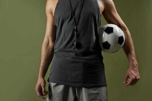 Árbitro de futebol adulto, caucasiano, com corpo musculoso, em pé dentro de casa