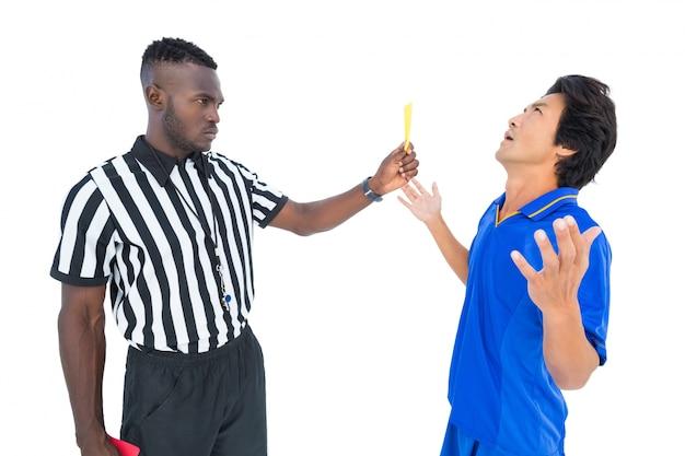 Árbitro grave mostrando o cartão amarelo ao jogador
