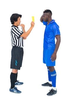 Árbitro mostrando cartão amarelo ao jogador de futebol