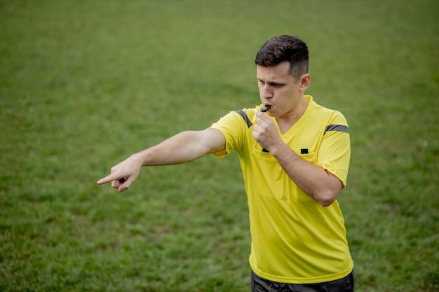 Árbitro mostrando penalidade durante o jogo. conceito de esporte, violação de regras, questões polêmicas, superação de obstáculos.
