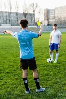 Árbitro sem rosto mostrando cartão amarelo ao esportista