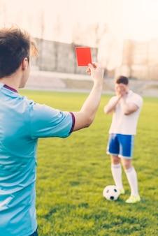 Árbitro sem rosto mostrando o cartão vermelho ao atleta