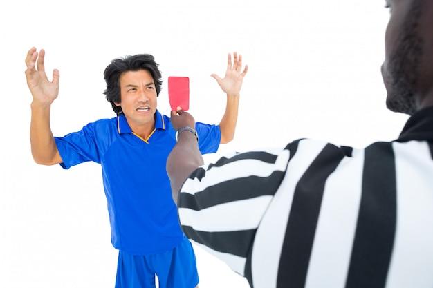 Árbitro sério mostrando o cartão vermelho ao jogador