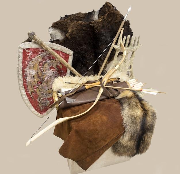 Arco, aljava de flechas, machado e escudo, peles de animais.