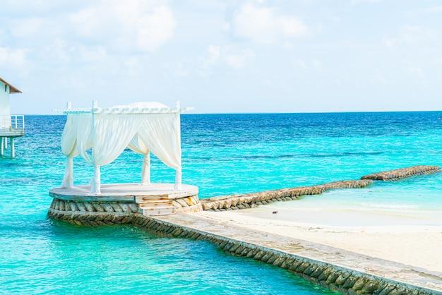 Arco branco com tropical resort das maldivas e mar