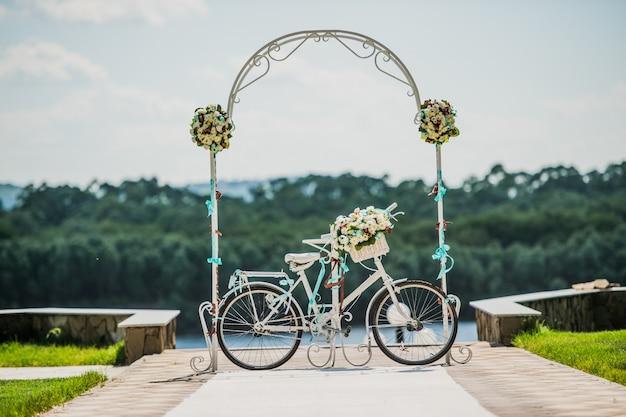 Arco branco e azul decorado com bicicleta de flores, registro de casamento ao ar livre