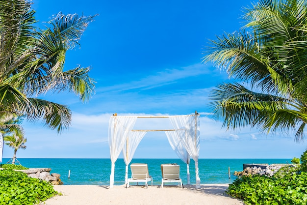 Arco branco e espreguiçadeiras na praia tropical