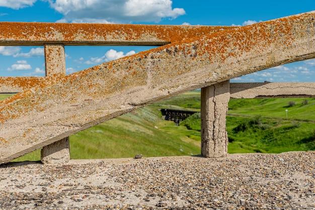 Arco coberto de líquen da ponte de concreto em scotsguard, sk com uma histórica ferrovia no fundo