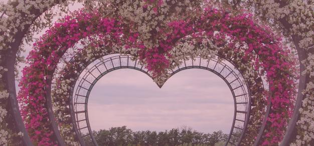 Arco da zona da foto com flores em forma de coração