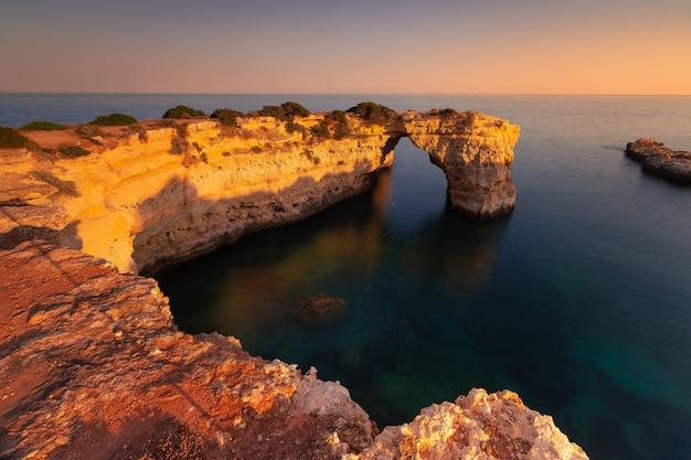 Arco de albandeira com luz do pôr do sol próximo a portimão, algarve, portugal.