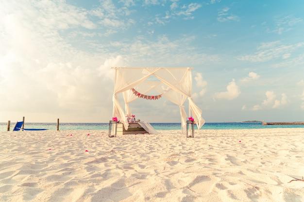 Arco de casamento na praia com mar e resort tropical das maldivas
