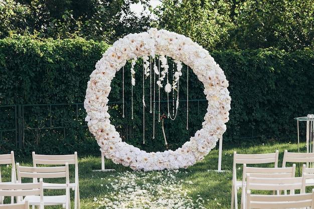 Arco de flores de casamento em formato redondo branco com miçangas e penas ao lado de cadeiras de madeira brancas na natureza