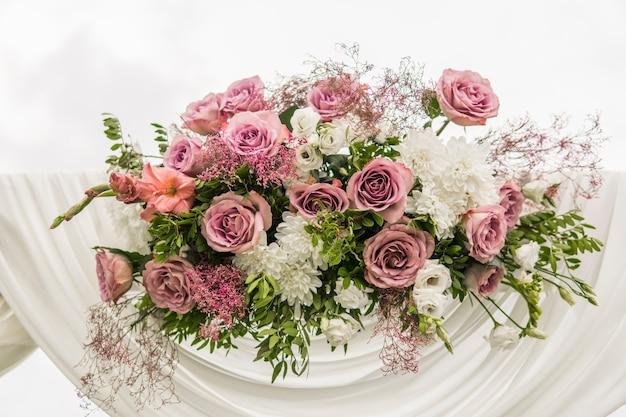 Arco de madeira floral com pano branco e flores brancas cor de rosa violetas frescas com folhas verdes em uma cerimônia de casamento rústica.