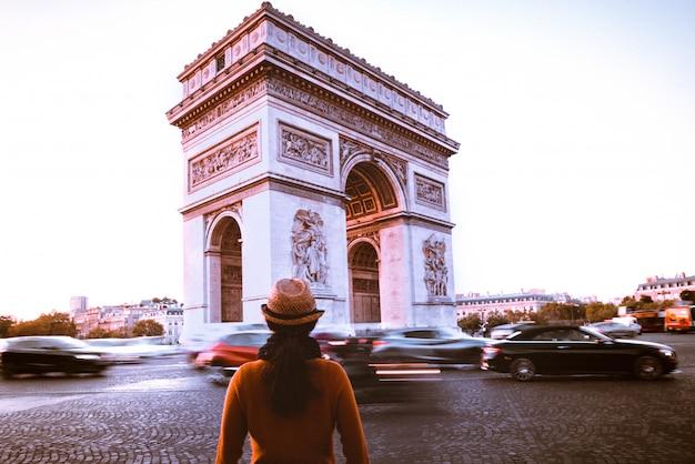 Arco do triunfo e viajante na rua de paris no crepúsculo da noite