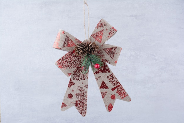 Arco festivo de natal com pinhas em fundo branco.