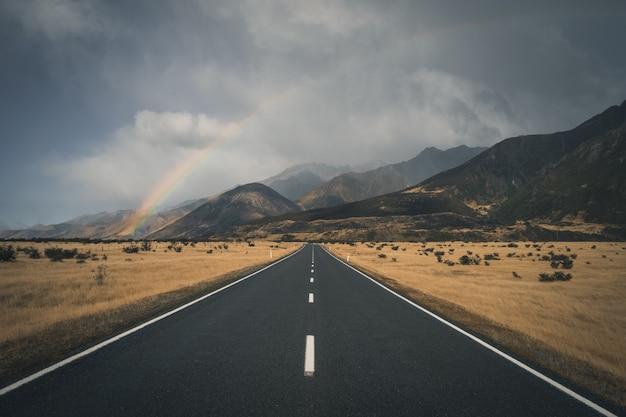 Arco-íris acima de uma estrada rural