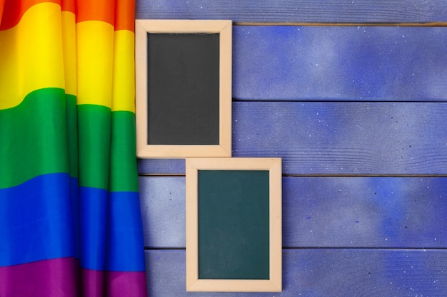 Arco-íris brilhante bandeira gay no espaço em branco e de madeira