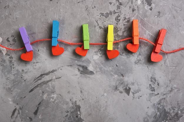 Arco-íris colorido prendedores de roupa de madeira e corações vermelhos em fundo cinza de concreto