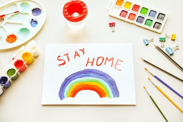 Arco-íris da pintura da menina no papel durante a quarentena de covid-19 em casa. ficar em casa