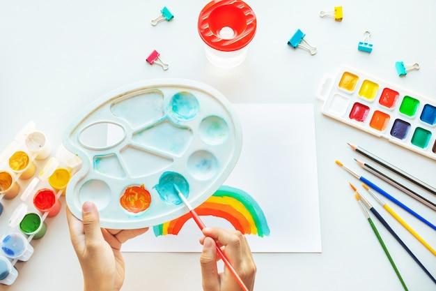 Arco-íris da pintura da menina no papel durante a quarentena de covid-19 em casa.