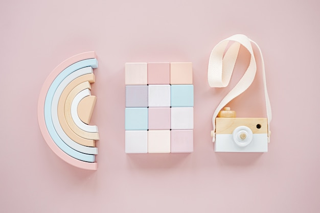 Arco-íris de madeira, blocos coloridos e câmera de brinquedo. brinquedos de bebê elegante em fundo rosa pastel. acessórios de brinquedos gratuitos de plástico ecológicos para crianças. camada plana, vista superior