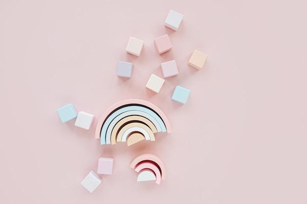 Arco-íris de madeira, blocos de brinquedo coloridos. brinquedos de bebê elegante em fundo rosa pastel. acessórios de brinquedos gratuitos de plástico ecológicos para crianças. camada plana, vista superior