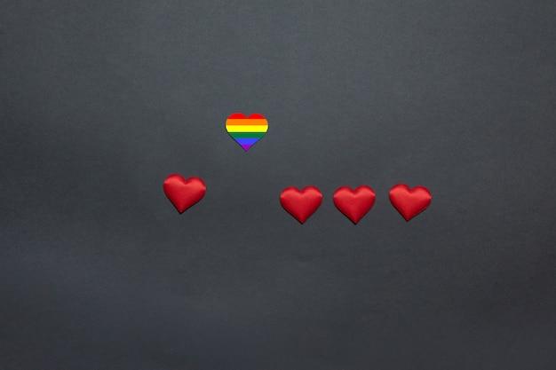 Arco-íris e corações vermelhos em um fundo amarelo, em uma vista superior e em um espaço para o texto. escolhendo um parceiro de amor