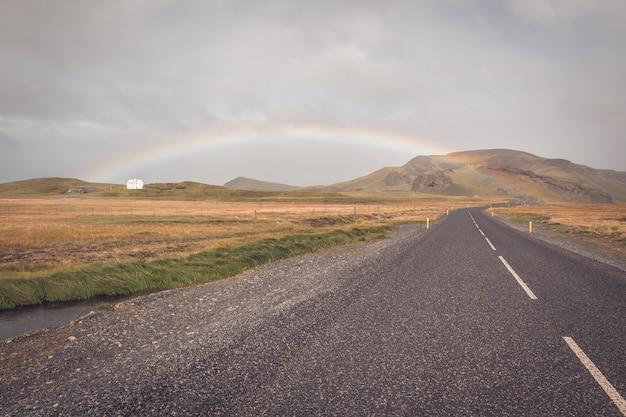 Arco-íris e estrada islandesa sem fim
