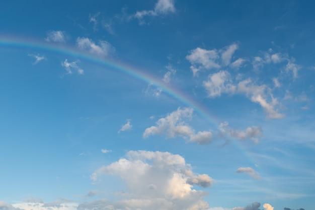 Arco-íris e nuvens brancas no céu azul
