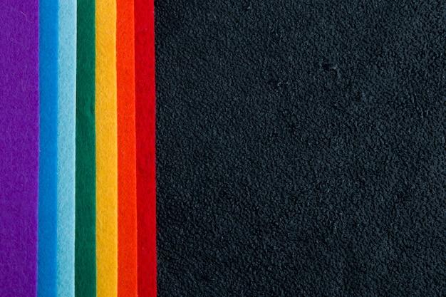 Arco-íris feltro em um fundo preto vista superior símbolo lgbt de gotas úmidas de água