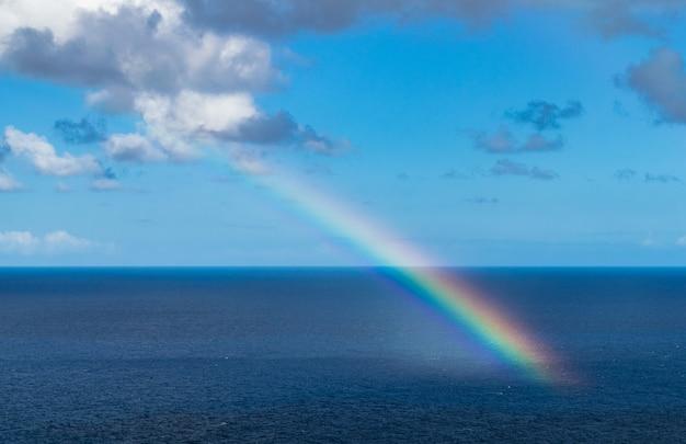 Arco-íris no oceano atlântico, com céu azul e nuvens