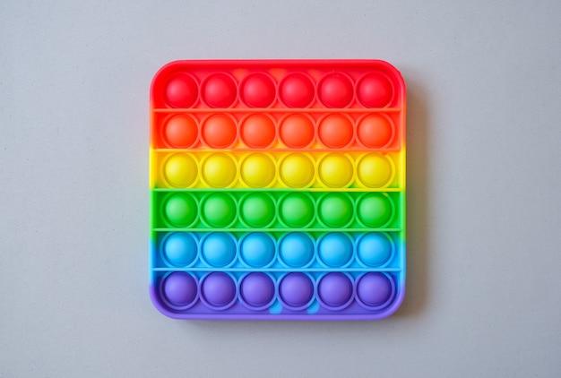 Arco-íris pop it toy fidget em um fundo de espaço vazio da cópia. fundo cinza