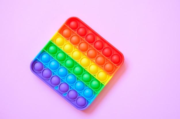 Arco-íris pop it toy fidget em um fundo de espaço vazio da cópia. fundo rosa